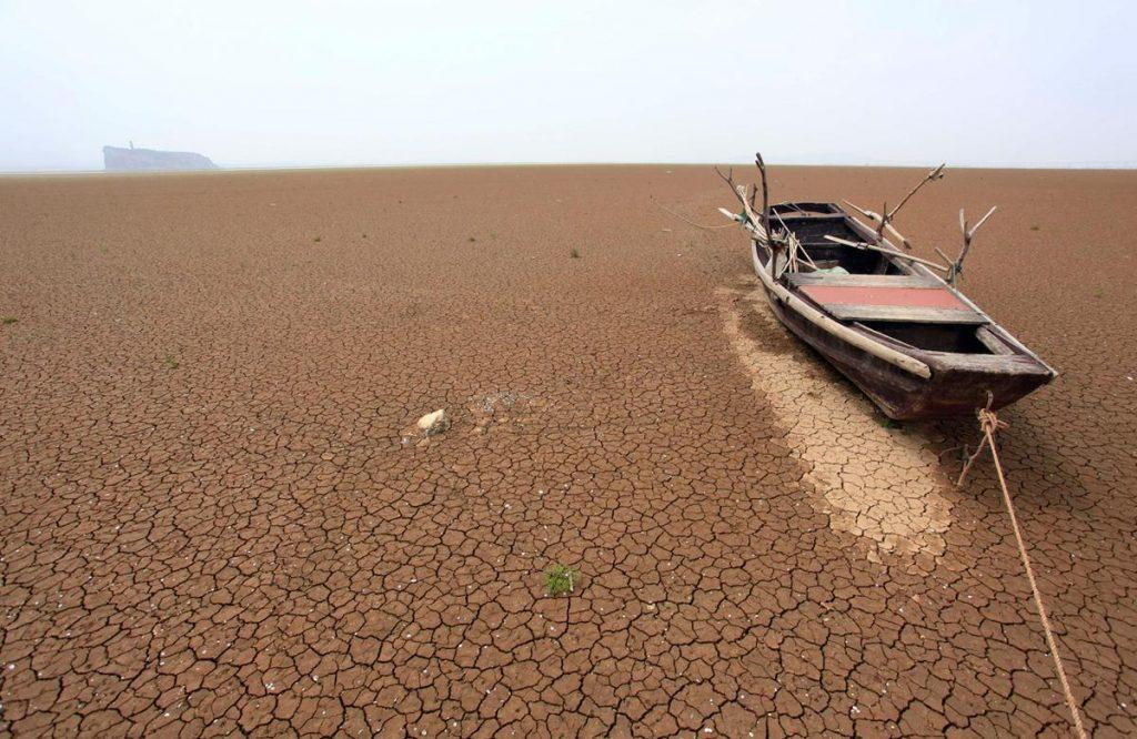 قایقی رها شده و پوسیده بر روی یک دریاچه خشک شده