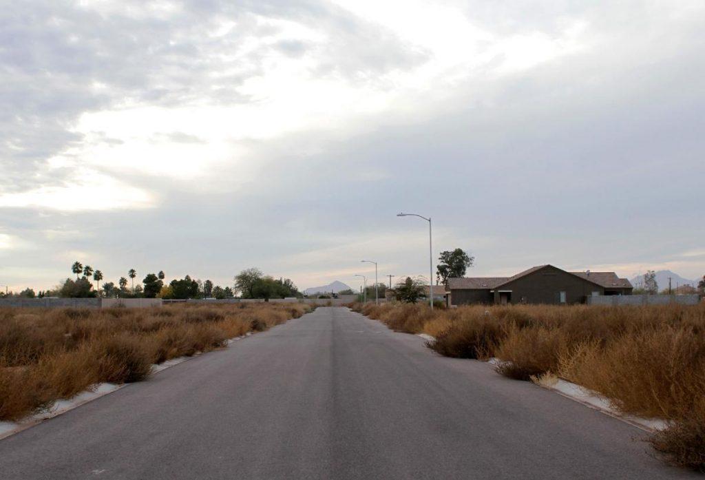 رشد علف های هرز در خیابان های یک جاده بدون تردد در آریزونا، آمریکا